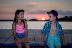 Girl and boy playing on the beach at sunset time royalty free stock images