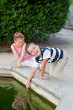 Girl and boy playing by the fountain Stock Photography