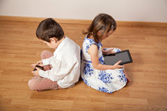 Girl and boy playing with gadgets Royalty Free Stock Image
