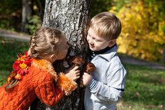 A girl and a boy are playing hide-and-seek royalty free stock images