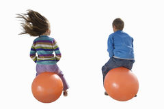 Girl and boy playing on inflatable hoppers, smiling, portrait, cut out Stock Photo