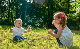Girl and boy playing with soap bubbles Stock Photography