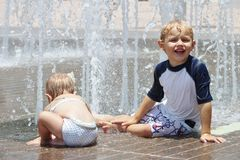 Girl and boy playing in a splash pad Stock Photography