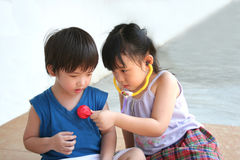 Girl & boy playing with stethoscope. Girl and boy playing with doctor's stethoscope toy Royalty Free Stock Images