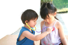Girl & boy playing stethoscope. Girl and boy playing toy stethoscope at leisure Royalty Free Stock Image