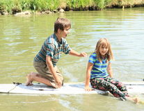 Girl and boy playing on surf Stock Photography