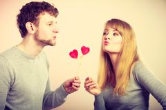 Girl with boy playing together. Love symbol romance relationship fun leisure concept. Girl with boy playing together. Youthful couple holding hearts smiling Stock Photography