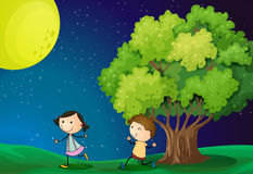 A girl and a boy playing under the bright fullmoon Royalty Free Stock Image