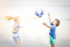 Girl and boy playing water ball on the beach Royalty Free Stock Photo