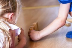 Girl and boy playing with wooden blocks - ready to tilt Stock Photos