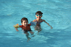 Girl & boy in the pool. Girl & boy floating in the swimming pool royalty free stock image