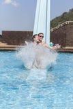 Girl Boy Pool Slide Splash Fun. Girl boy teenagers at beach pool slide splash summer holidays laughter swimming happy fun Stock Image