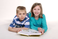 Girl and boy reading book. Stock Photo
