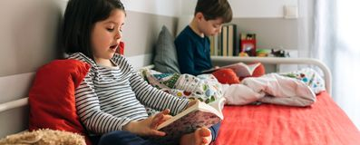 Girl and boy reading a book Royalty Free Stock Image