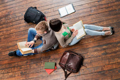 Girl and boy reading books leaning on each other on wooden floor Royalty Free Stock Images
