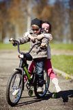 Girl and boy riding on bicycle Stock Photos