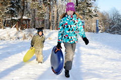 Girl and boy riding with hills on sleds Stock Images