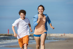 Girl and boy running on beach. Teenage girl and boy running, jumping on beach Royalty Free Stock Photography