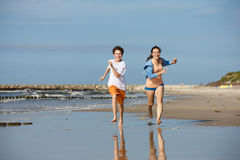 Girl and boy running on beach. Teenage girl and boy running, jumping on beach Royalty Free Stock Photos