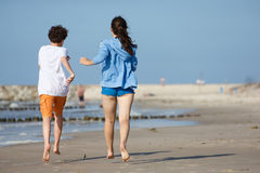 Girl and boy running on beach. Teenage girl and boy running, jumping on beach Royalty Free Stock Image