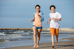 Girl and boy running on beach. Teenage girl and boy running, jumping on beach Royalty Free Stock Photography