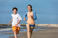Girl and boy running on beach. Teenage girl and boy running, jumping on beach Stock Photo