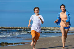 Girl and boy running on beach Stock Image