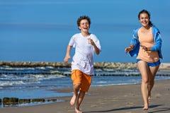 Girl and boy running on beach Stock Image