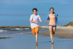 Girl and boy running on beach Royalty Free Stock Images