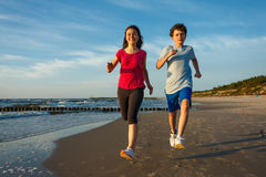 Girl and boy running on beach. Teenage girl and boy running, jumping on beach Stock Photos