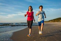 Girl and boy running on beach Stock Photos