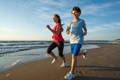 Girl and boy running on beach. Teenage girl and boy running, jumping on beach Royalty Free Stock Image