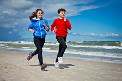 Girl and boy running on beach. Teenage girl and boy running, jumping on beach Stock Photo