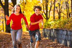 Girl and boy running, jumping in park. Girl and boy playing in autumn park Royalty Free Stock Photos