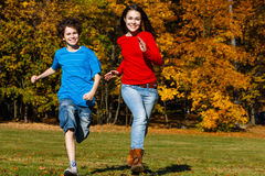 Girl and boy running, jumping in park. Girl and boy playing in autumn park Stock Images