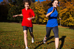 Girl and boy running, jumping in park. Girl and boy playing in autumn park Royalty Free Stock Photo
