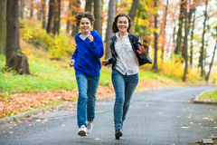 Girl and boy running, jumping in park Stock Photography