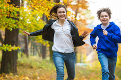 Girl and boy running, jumping in park Royalty Free Stock Photos