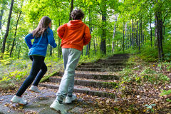 Girl and boy running, jumping in park Stock Image