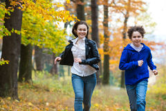 Girl and boy running, jumping in park Stock Photos