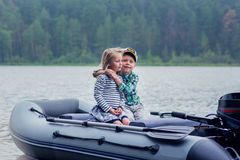 Girl and boy`s best friend sailing boat on the lake a summer day Stock Photos