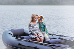 Girl and boy`s best friend sailing boat on the lake a summer day Stock Images
