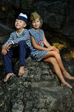Girl and boy sailors sitting on a stone royalty free stock photo