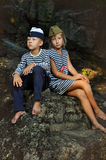 Girl and boy sailors sitting on a stone stock photos