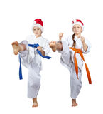 Girl and boy in Santa Claus caps beat kick leg forward Royalty Free Stock Photo