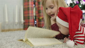 Girl and boy in a Santa hat reading a book in front of the Christmas tree. Small girl and boy reading a book in front of the Christmas tree stock video