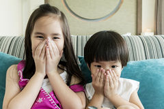 Girl and boy shutting up thier mouthes Stock Photos