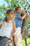 Girl and boy sit on caudex of lilac and look aside royalty free stock image