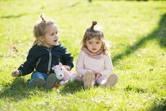 Girl and boy sit on green grass stock photos
