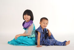 Girl and boy sitting back to back. A little asian girl and boy with cute and happy facial expression sitting back to back in white background and having great Stock Photo